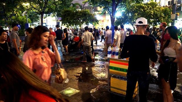 Nước chảy ra từ một hàng bán nước giải khát, nhiều du khách qua lại, giẫm chân lên kéo nước lan rộng nhìn con đường rất mất mỹ quan