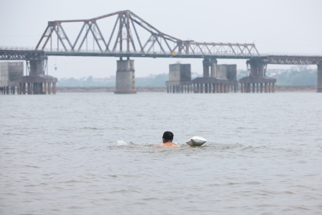 Cũng như mọi ngày, ông Phúc bơi ngược về phía cầu Long Biên, vòng đi vòng lại hàng km.