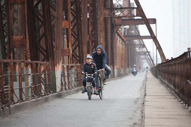 Cũng trong buổi sáng mùng 1 Tết Đinh Dậu, nhiều người Hà Nội khác cũng chọn rèn luyện thể thao là việc làm khai xuân. Trong ảnh là hai cha con đang đạp xe qua cầu Long Biên, khi thành phố vẫn còn trong giấc ngủ muộn sau đêm Giao thừa.