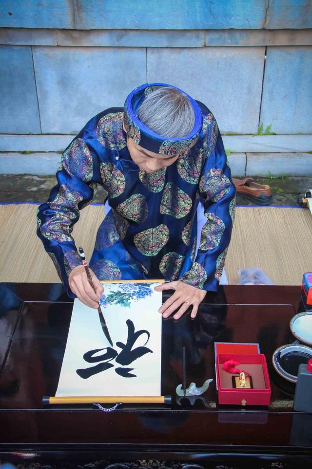 Ông đồ Nguyễn Phước Hải Trung, Phó Giám đốc Trung tâm Bảo tồn Di tích Cố đô Huế đang cho chữ may mắn đầu năm Đinh Dậu 2017
