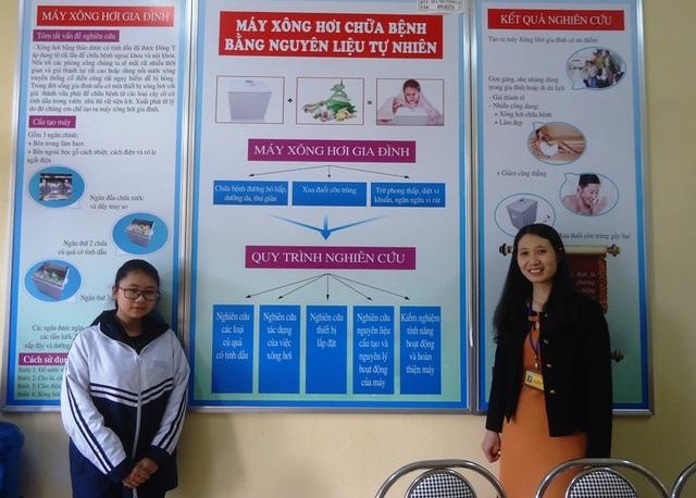 Nữ sinh Nguyễn Thanh Tâm và cô giáo bên mô hình sơ đồ máy xông hơi chữa bệnh bằng nguyên liệu tự nhiên