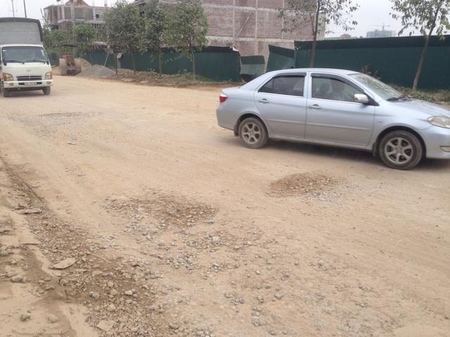 Thật khó hình dung đây là đoạn đường bê tông vì nó đã bị phủ một lớp đất bụi dày đặc cùng lởm chởm đá dăm, chỉ cần một chiếc xe đi qua là bụi tung lên mù mịt.