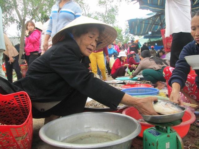 Một cụ bà đang chọn cá tươi cho ngày mùng 3 Tết cúng đưa ông bà