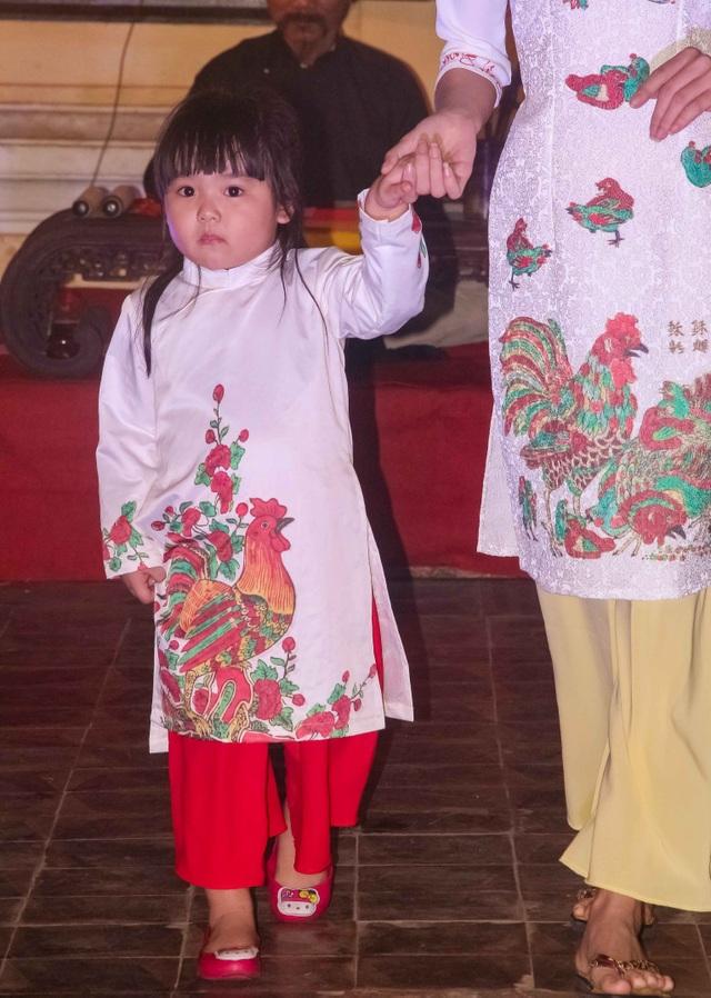 Em bé mặc chiếc áo dài với con gà trống đỏ