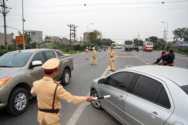 Lực lượng CSGT vừa tuýt còi vừa hướng dẫn các xe di chuyển vào đền Trần đỗ đúng bãi gửi xe