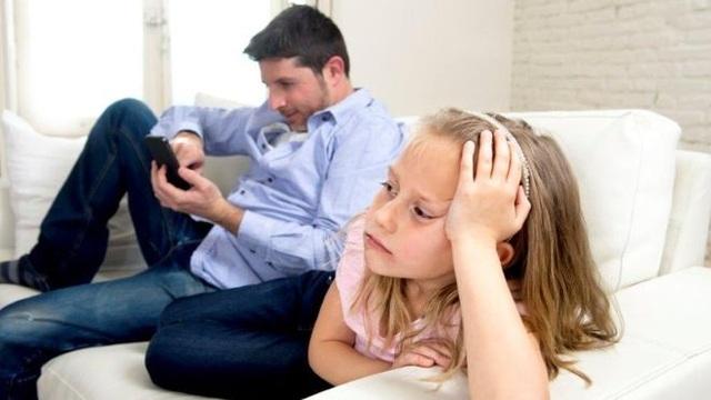 Cha mẹ liên tục sử dụng điện thoại di động có thể khiến trẻ em cảm thấy buồn bã và bị bỏ rơi. (Ảnh: theo BBC)