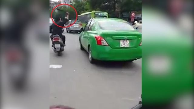 Nam thanh niên cầm mã tấu chặt kiếng chiếu hậu của một ô tô đang lưu thông