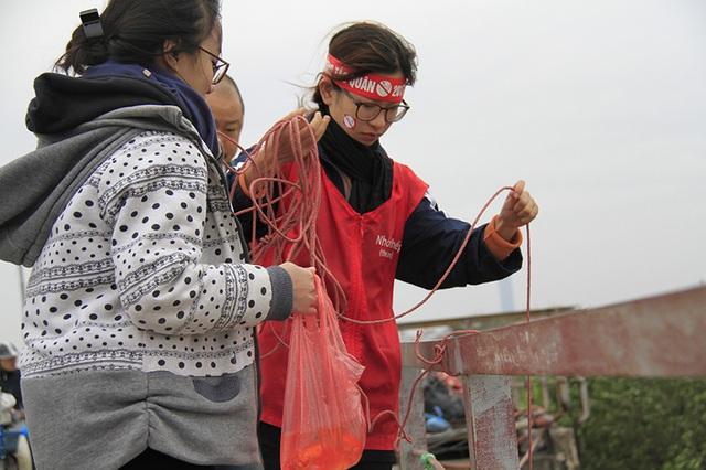 Nhóm sinh viên tình nguyện chuẩn bị bảng hiệu, dây thừng, thùng nhựa để hỗ trợ bà con thả cá chép trong ngày tiễn ông Táo về trời