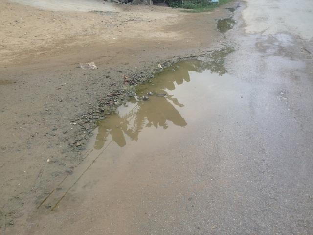 """Mỗi khi mưa xuống, nước lại ứ đọng trên mặt đường. Những ổ gà, ổ voi trở thành những """"vũng tử thần"""" giăng bẫy người tham gia giao thông."""