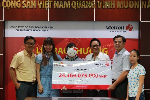 Khách hàng trúng thưởng bà Thư (đeo mặt nạ) chụp ảnh cùng nghệ sĩ Tấn Hoàng (đeo kính), các nhà báo và đại lý/điểm bán hàng phát hành vé trúng giải Jackpot