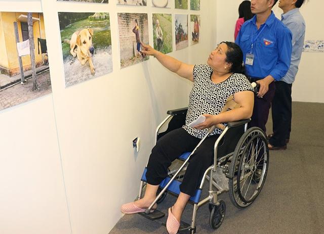 Chị Phạm Thị Hoa (Thái Nguyên) đang giới thiệu 1 trong số 17 bức ảnh chị chụp tại triển lãm.