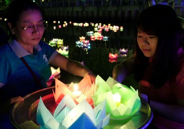 Để tránh chen lấn do đông người, chùa Pháp Hoa bố trí người hỗ trợ nhận hoa đăng của mọi người rồi xếp vào mâm để đưa xuống sông.