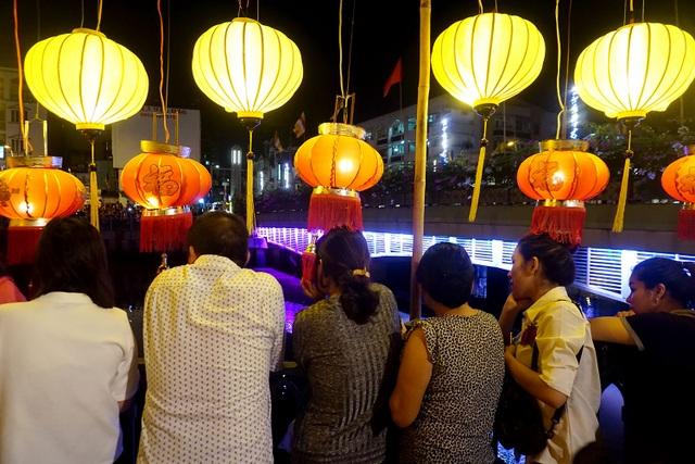 Nhiều người đứng trên kênh chiêm ngưỡng vẻ đẹp lung linh huyền ảo trong đêm Phật đản và ghi lại khoảnh khắc đáng nhớ này.