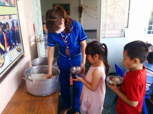 Cô Hoa hướng dẫn cho các em học sinh mầm non ăn tại trường - (Ảnh: NVCC)