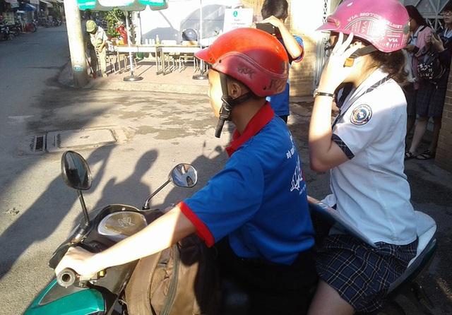 Một nữ sinh được sinh viên tình nguyện chở về nhà lấy máy tính tại điểm thi THCS Nguyễn Văn Phú (Q.11, TP.HCM).
