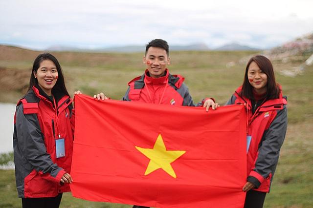 3 sinh viên của Học viện Ngoại giao mang lá cờ Việt Nam tung bay trên thượng nguồn sông.