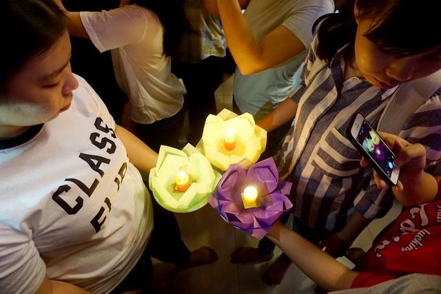 Các bạn trẻ dùng điện thoại ghi lại hình ảnh chiếc hoa đăng trên tay.