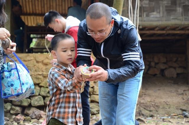 Em nhỏ thích thú khi được bố dạy cách chơi quay của người dân tộc vùng cao.
