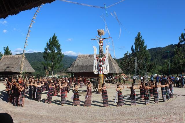 Các nam nữ Cơtu trong trang phục truyền thống sặc sỡ múa điệu tung tung - da dá quanh cây nêu đã được dựng