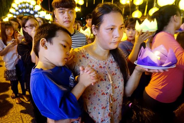 Cậu bé theo mẹ đến chùa, học theo mẹ chắp tay cầu khấn.