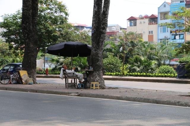 Dưới bóng cây xà cừ cổ thụ ở vỉa hè đường Láng, những quán cắt tóc vỉa hè còn mở thêm ô dù để tránh bớt cái nắng nóng của mùa hè đang đến.