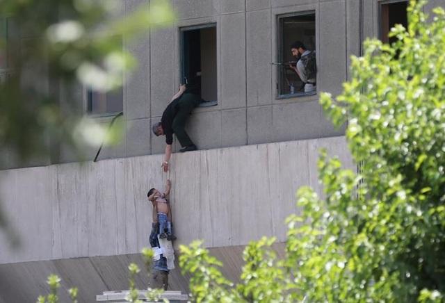 Một em bé được thả qua cửa sổ tòa nhà quốc hội Iran trong vụ tấn công khủng bố ở thủ đô Tehran, Iran. Hai vụ tấn công xảy ra gần như đồng thời hôm 7/6 đã khiến tổng cộng 12 người chết. (Ảnh: Reuters)