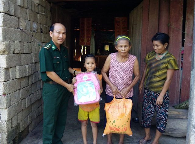 Đại uý Nguyễn Văn Vỹ (người đứng ngoài cùng bên trái ảnh) tặng cặp sách, gạo cho học trò và gia đình. Anh hiện đang đỡ đầu cho 3 học sinh nghèo để các em có điều kiện cắp sách tới trường.