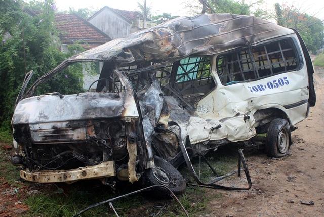 Xe ô tô tải hai biển số, không chủ nhân bị biến dạng và bốc cháy sau khi bị tàu lửa tông.