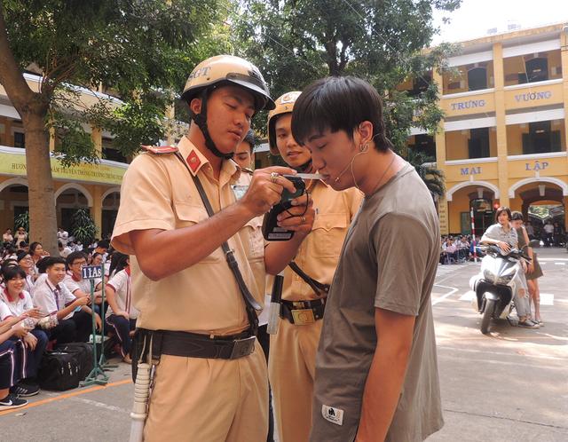 Cảnh sát thực hiện đo nồng độ cồn một học sinh tham gia giao thông có dấu hiệu uống bia rượu...
