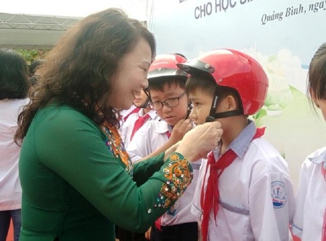 Thứ trưởng Bộ Giáo dục và Đào tạo Nguyễn Thị Nghĩa tặng mũ bảo hiểm cho các em học sinh Quảng Bình