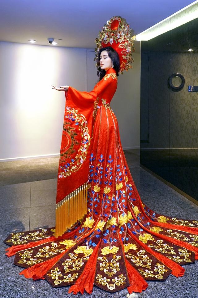Chất liệu được sử dụng cho bộ áo dài là vải gấm, tông màu đỏ vàng để tôn lên sự uy nghi và sang trọng. Huyền My cho biết cô rất tự tin về bộ trang phục này và mong muốn được truyền tải tinh thần dân tộc thông qua áo dài truyền thống.
