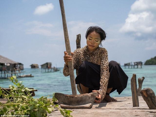 Một cô gái giã bột để bôi lên mặt. Đây là thứ bột tự chế giúp chống lại thứ nắng gay gắt trên biển