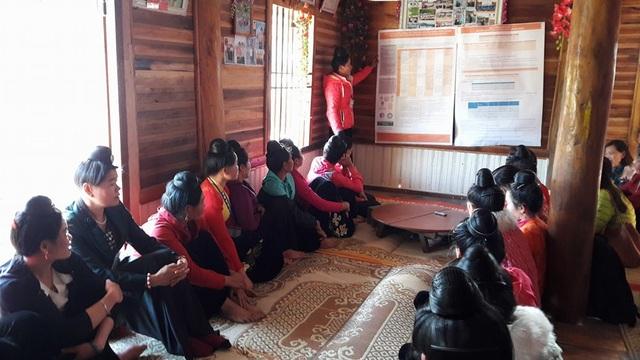Chị Lò Thị Dương đọc bản tin dự báo thời tiết mùa cho chị em trong bản Phăng 1 cùng nghe