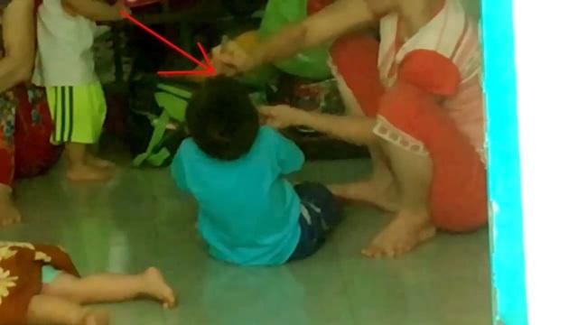 Bảo mẫu đánh đập trẻ trong lúc ăn. (Ảnh chụp từ clip)