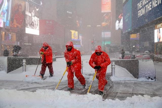 Các công nhân hối hả dọn tuyết trên Quảng trường Thời đại