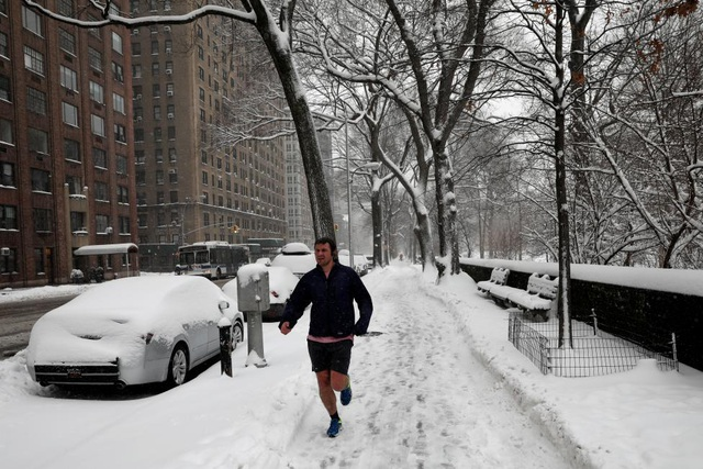 Một người đàn ông chạy bộ trên vỉa hè cạnh công viên Central Park ở New York, nơi ghi nhận hiện tượng tuyết rơi dày gần 30cm vào hôm qua