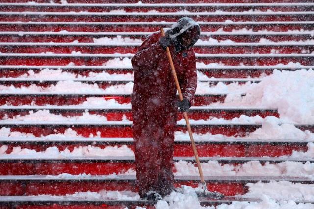 Một công nhân dọn tuyết trên các bậc cầu thang ở Manhattan