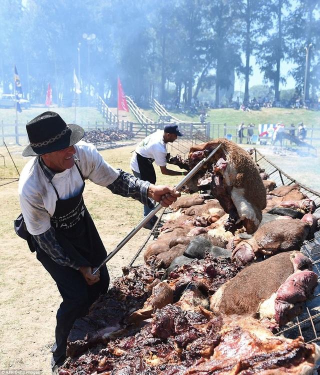 Một đầu bếp nam nâng tảng thịt lớn bằng tay