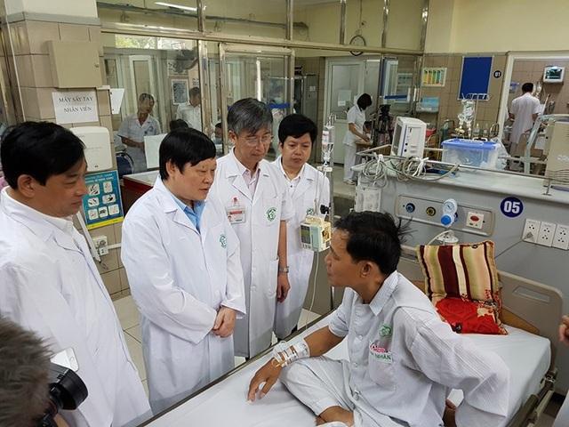 Thứ trưởng Bộ Y tế Nguyễn Viết Tiến (đứng thứ 2 từ trái sang) hỏi thăm bệnh nhân Quang vừa từ bệnh viện Đa khoa Hòa Bình chuyển về Bạch Mai (Hà Nội) - Ảnh: Hồng Hải
