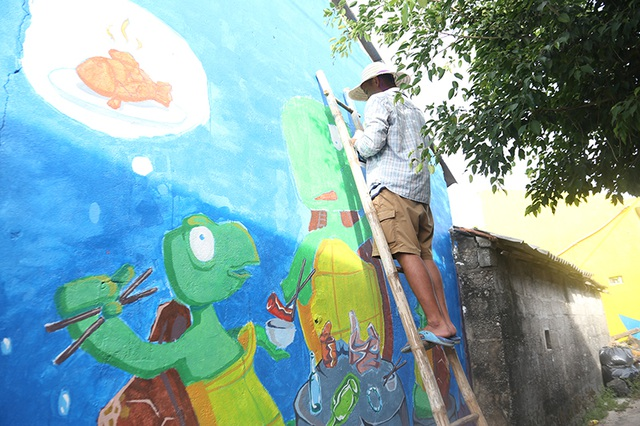 """Họa sĩ Kim Hoàn (Hà Nội) lựa chọn phong cách hoạt hình cho bức tranh """"Rùa ăn cá gỗ"""" của mình"""