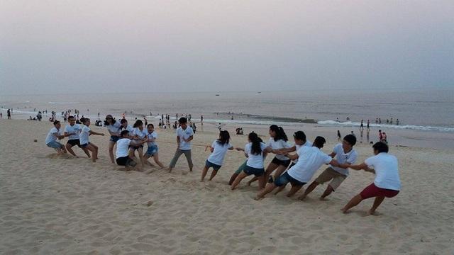Một nhóm bạn trẻ chơi kéo co trên bãi biển