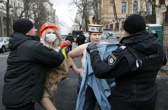Cảnh sát ngăn cản cuộc biểu tình của các nhà hoạt động thuộc nhóm nữ quyền Femen ở gần trụ sở tòa nhà tổng thống tại Kiev, Ukraine ngày 21/11.