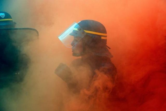 Nữ cảnh sát chống bạo loạn của Pháp đối mặt với các công nhân tại các nhà máy thép trong cuộc biểu tình ở thủ đô Paris ngày 13/10.