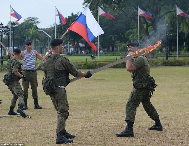 """Binh sĩ Nga tập khả năng chịu nóng bằng việc """"đấu"""" trực tiếp với thanh gỗ đang cháy (Ảnh: AFP)"""