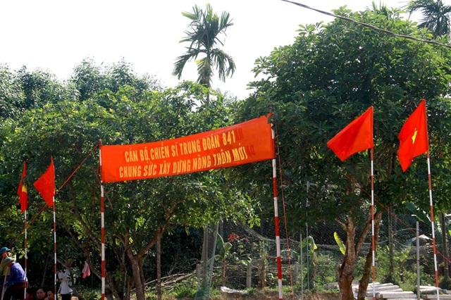 Cờ đỏ sao vàng, băng rôn cổ động khích lệ thêm tinh thần lao động, chiến đấu vì dân của cán bộ, chiến sĩ Trung đoàn 841 và Ban chỉ huy quân sự huyện Cẩm Xuyên tại thôn Na Trung, xã Cẩm Thạch, huyện Cẩm Xuyên.