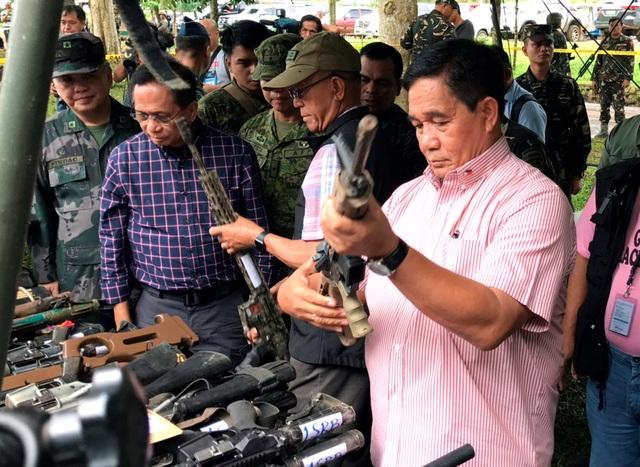 """Mặc dù gặp nhiều khó khăn nhưng quân đội Philippines vẫn tự tin có thể giành chiến thắng trước các phiến quân tại Marawi. """"Trong một vài ngày tới, chiến sự có thể chấm dứt"""", Tham mưu trưởng quân đội Eduardo Ano nhận định. Trong ảnh: Bộ trưởng Quốc phòng Philippines Delfin Lorenzana (giữa) cùng các tướng lĩnh quân đội kiểm tra hơn 100 khẩu súng và đạn dược thu được từ nơi ẩn náu của các phiến quân thân IS ở Marawi. (Ảnh: Reuters)"""