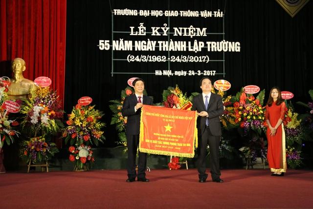 Bộ trưởng Bộ GD&ĐT Phùng Xuân Nhạ trao cờ thi đua của Chính phủ cho PGS. TS Nguyễn Ngọc Long, Hiệu trưởng, đại diện nhà trường