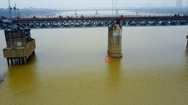 Quả bom nằm dưới lòng sông sâu khoảng 6m nước, cách trụ P13 của cầu Long Biên khoảng 5m.