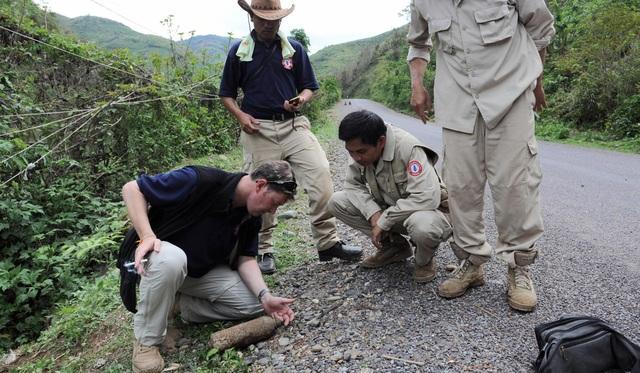 Các thành viên của Mag Vietnam kiểm tra một vật liệu chưa nổ (Ảnh: AFP)