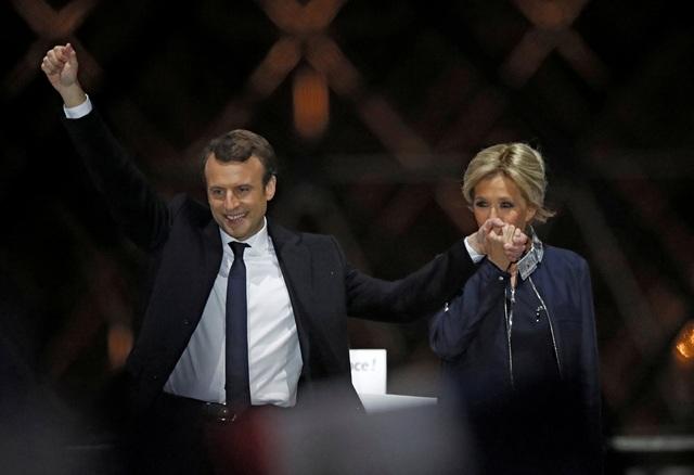 Bà Brigitte Trogneux hôn tay chồng trong đêm ăn mừng chiến thắng bầu cử hôm 7/5 (Ảnh: Reuters)